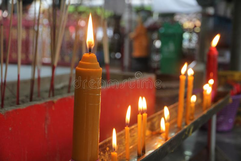Lighted candle and incense for Buddha. Selective focus. Buddhists make merit,Placing a lighted candle and lit incense with candles frame on the altar of Buddha royalty free stock photography