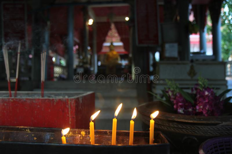 Lighted candle and incense for Buddha. Selective focus. Buddhists make merit,Placing a lighted candle and lit incense with candles frame on the altar of Buddha royalty free stock photo
