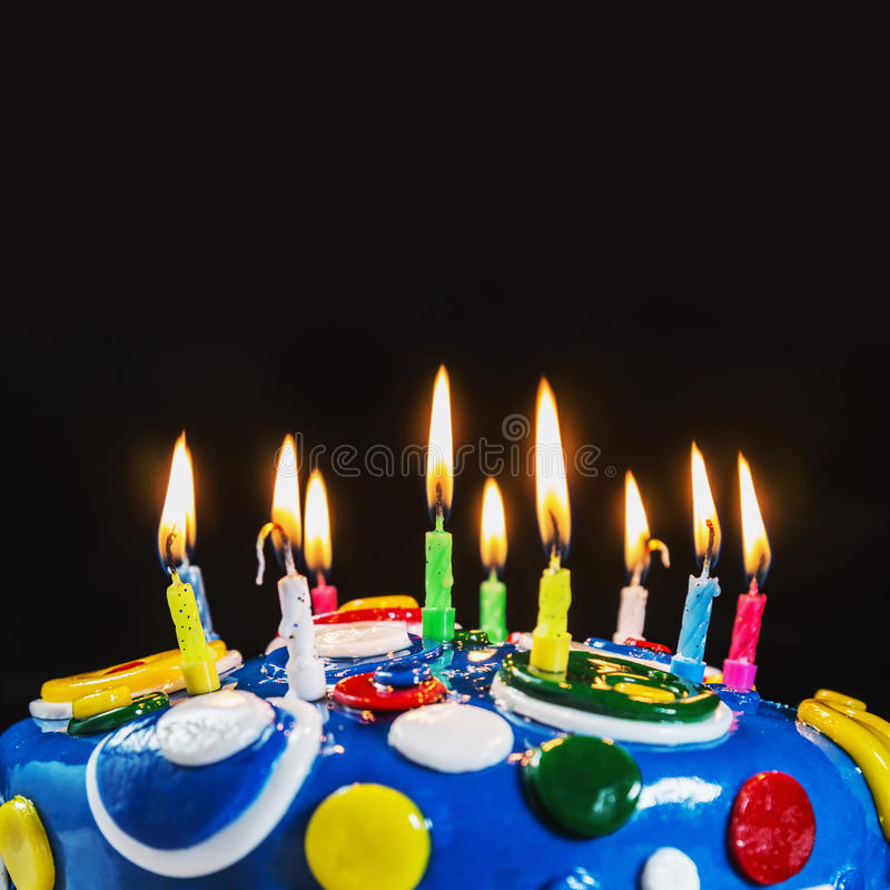 Lighted candles on a birthday cake. Focus on green-blue candle royalty free stock photo