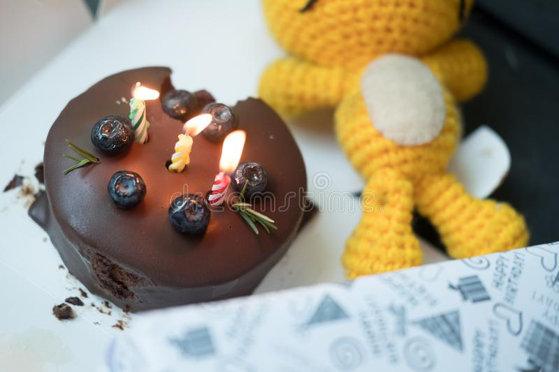 Lighted candles on a birthday chocolate cake stock photo