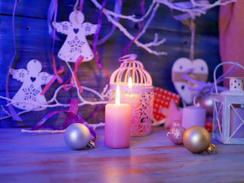 Lighted candles, decorative lights, balls, Christmas decor on a wooden table, wooden background. Pink color, interior composition, romantic evening atmosphere stock images