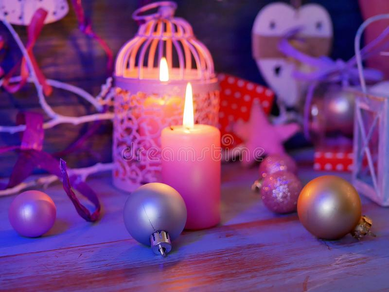 Lighted candles, decorative lights, balls, Christmas decor on a wooden table, wooden background. Pink color, interior composition, romantic evening atmosphere stock image
