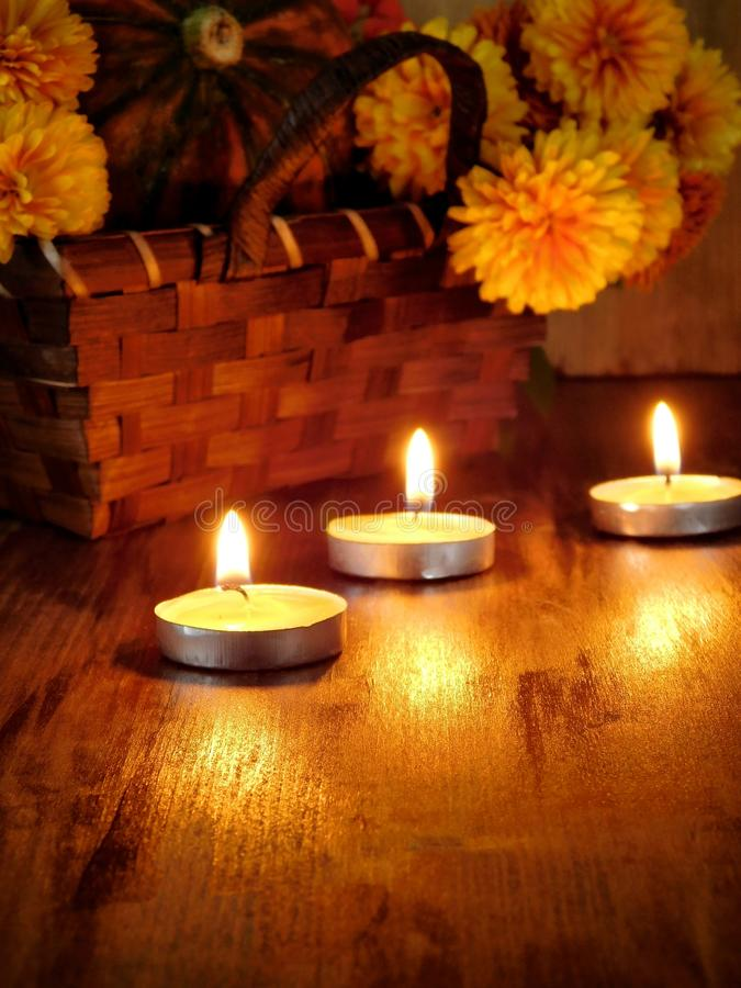 Lighted candles and a wicker basket with a pumpkin and flowers in the background. Three lighted candles on a wooden table and a wicker basket with a pumpkin and royalty free stock image