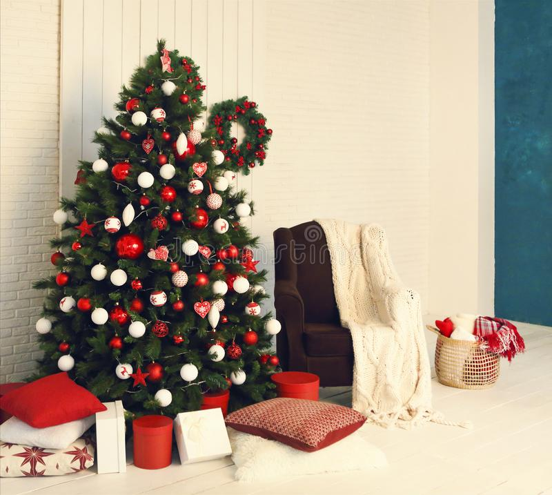 Lighted Christmas tree with presents underneath in living room stock photo