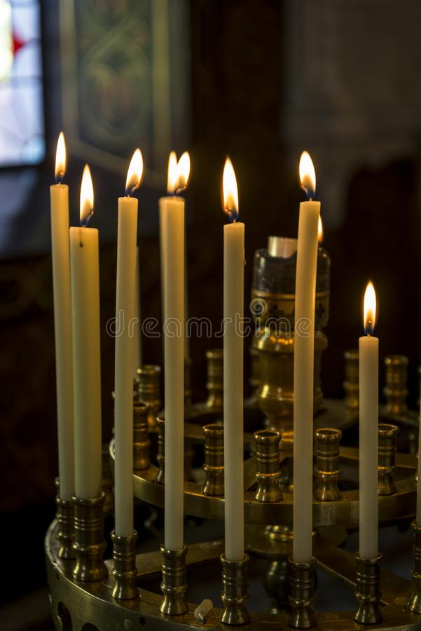 Lighted church candles. Atmospheric shot of thin, upright lighted church candles in an Russian Orthodox church royalty free stock images