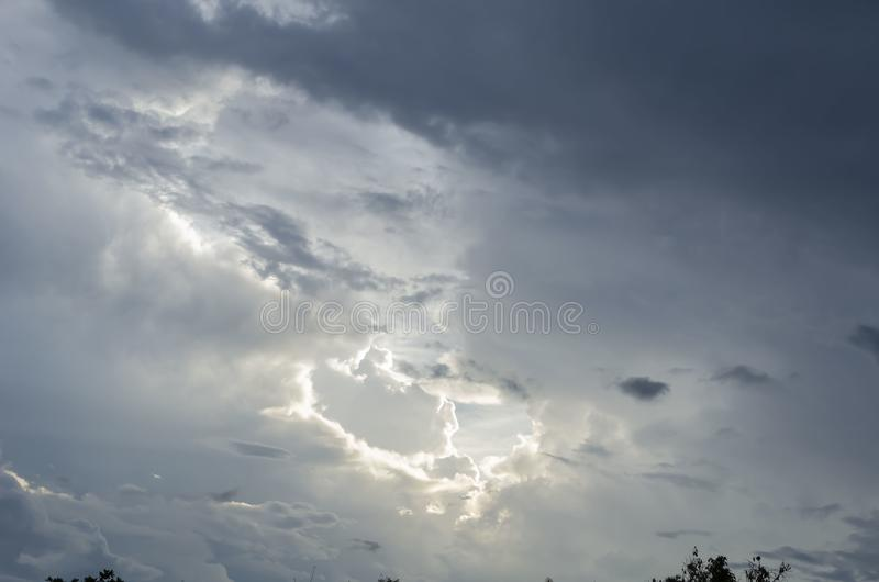 Lighted Cloud Opening. Dark rain clouds suspended in the sky after a downpour of rain. A lighted area from an opening in the cloudy sky near to the sun stock image
