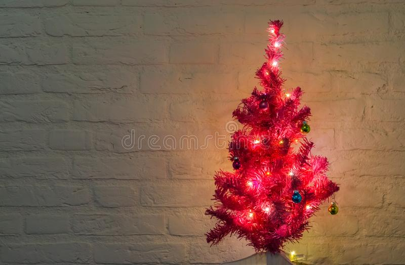 Lighted and decorated christmas tree isolated on a white brick wall background. A lighted and decorated christmas tree isolated on a white brick wall background stock photos