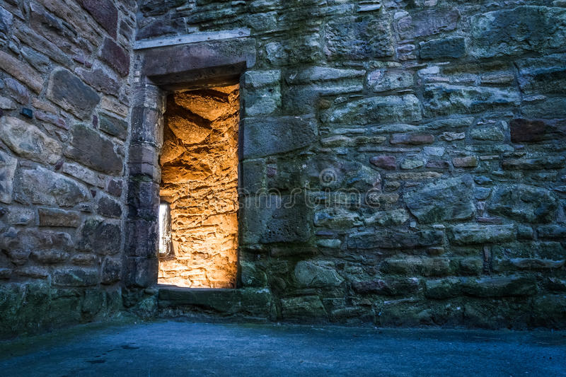 Lighted dorway to the ancient castle stock photo