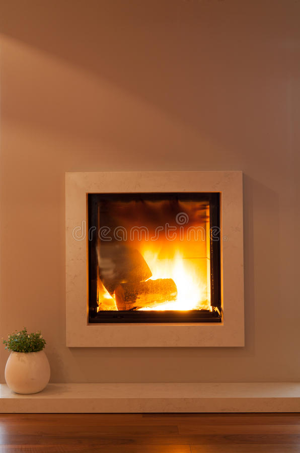 Lighted fireplace. Warm lighted fireplace in modern lounge stock photos