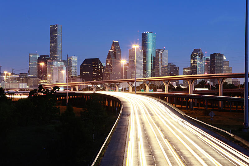 Lighted Houston skyline against blue sky. Highways leading to Lighted Houston skyline against blue evening sky stock photo