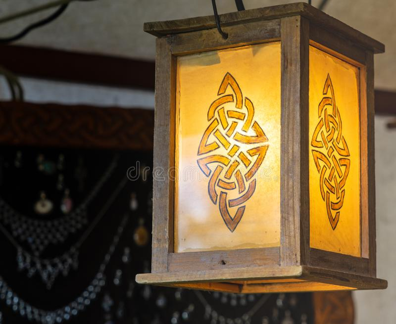 Lighted lantern with an abstract pattern resembling a rune, wooden frame with yellow glass. Craft stock photos