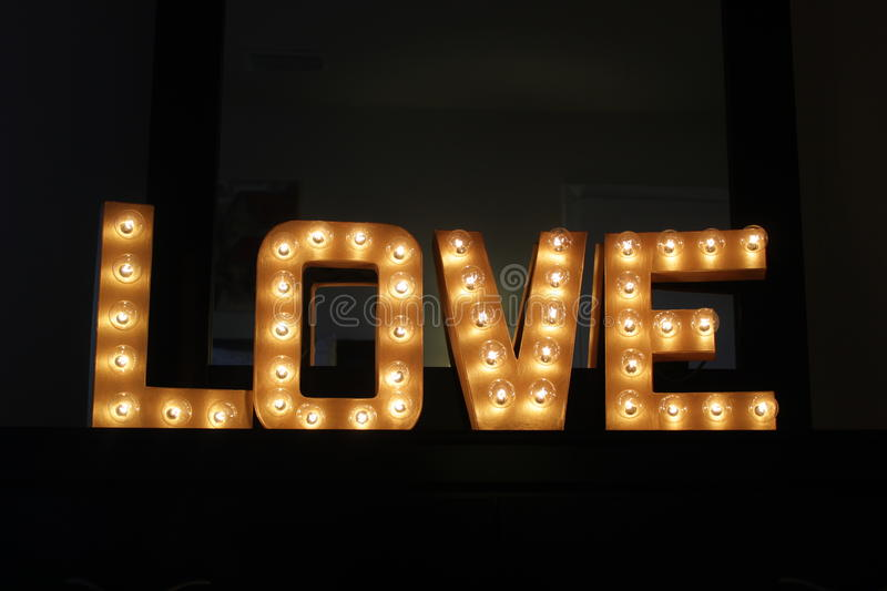 Lighted Love Sign. Gold Lighted LOVE marquee sign royalty free stock image