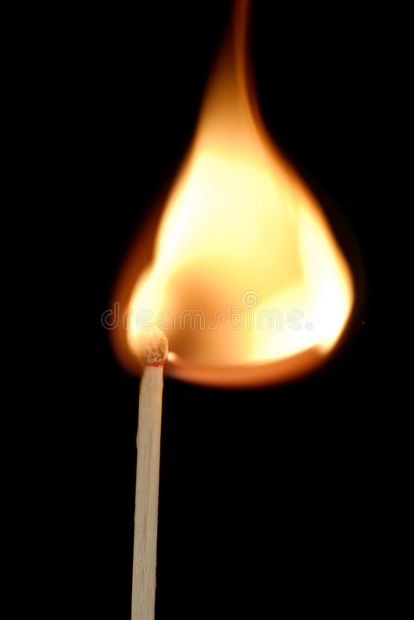 Lighted match. Macro view of lighted match with black background and copy space royalty free stock photography