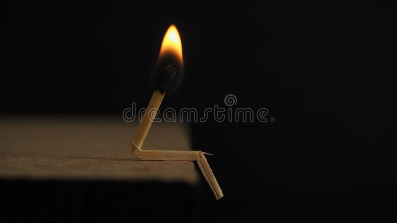 Lighted Matchstick on Brown Wooden Surface royalty free stock image