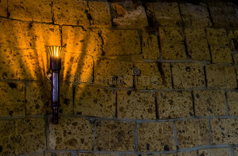 Lighted medieval castle torch hanging on a stone wall, vintage objects and background. A lighted medieval castle torch hanging on a stone wall, vintage objects royalty free stock images