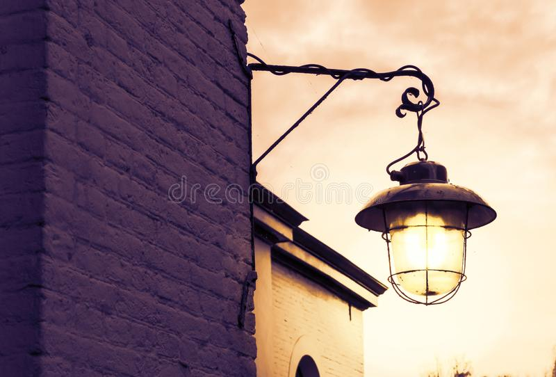 Lighted old and dirty lantern shining bright light at night. A lighted old and dirty lantern shining bright light at night royalty free stock photos