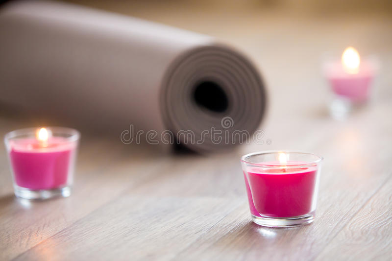 Lighted pink candle and rolled brown yoga, pilates mat on the fl stock photos