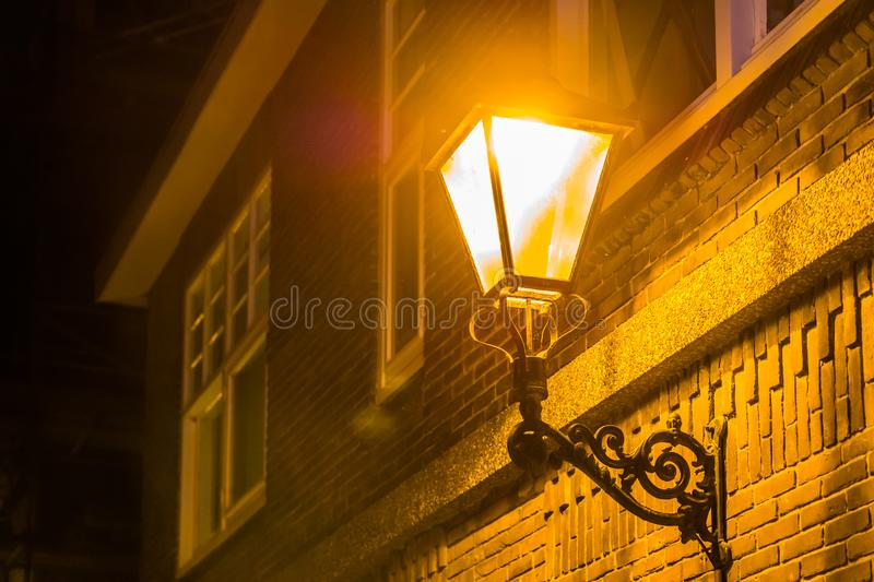 Lighted street lantern on the wall of a house at night, city scenery in the evening, vintage decoration stock photos