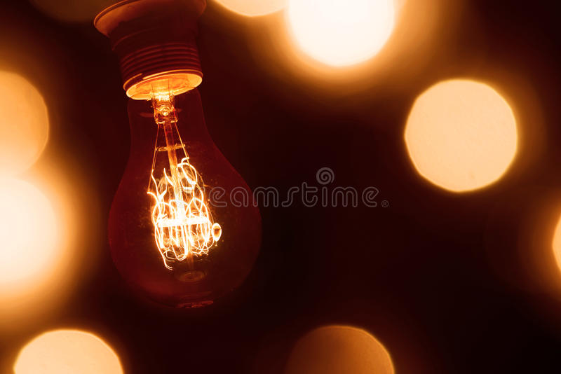 Lighted vintage incandescent bulb stock photography