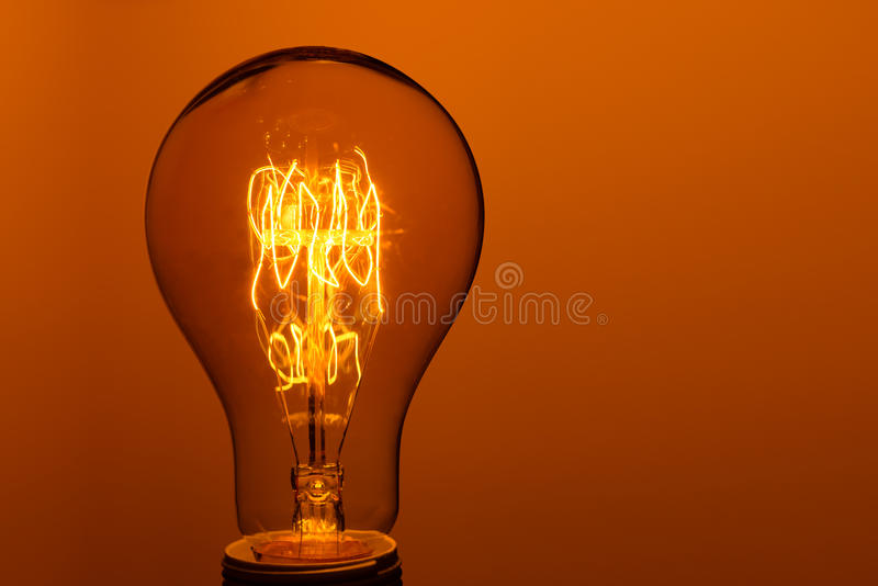 Lighted vintage incandescent bulb. On orange background royalty free stock photography