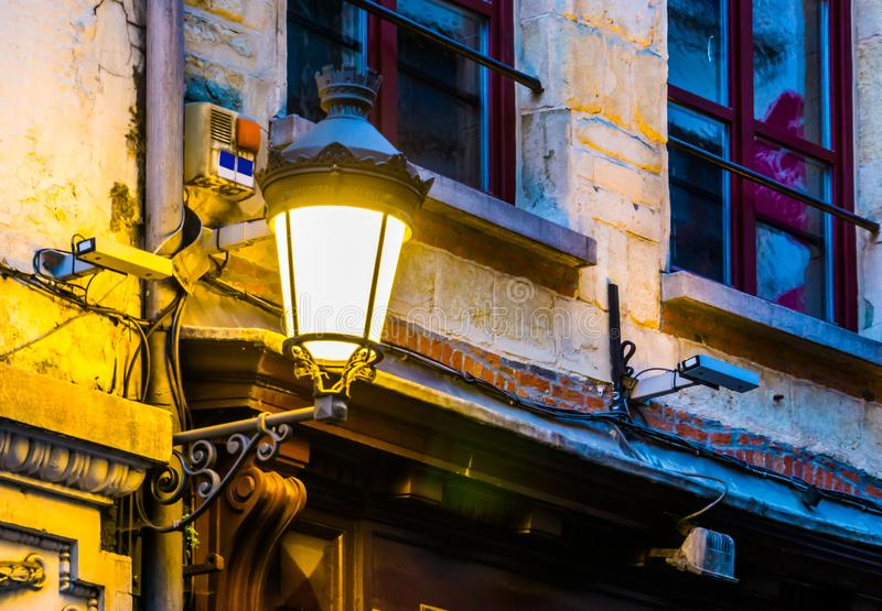 Lighted vintage street lantern on the wall of a city house, Flemish architecture, outdoor lighting. A lighted vintage street lantern on the wall of a city house stock photo