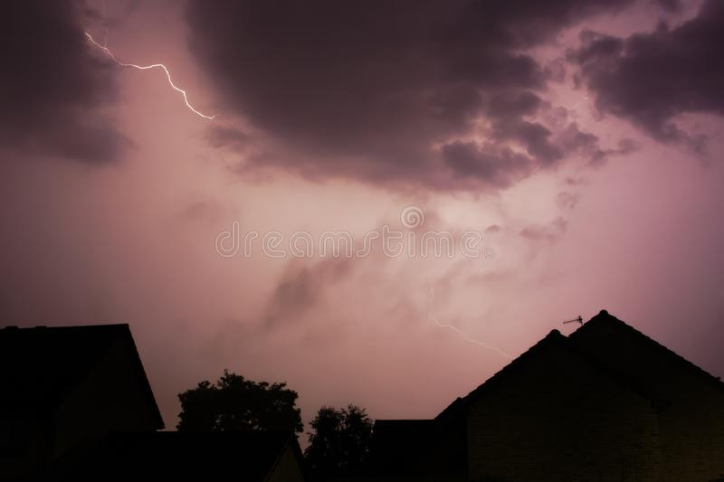 Lightening bolt over houses in the middle of a storm. A lightening bolt flashes across the sky above some houses royalty free stock photos