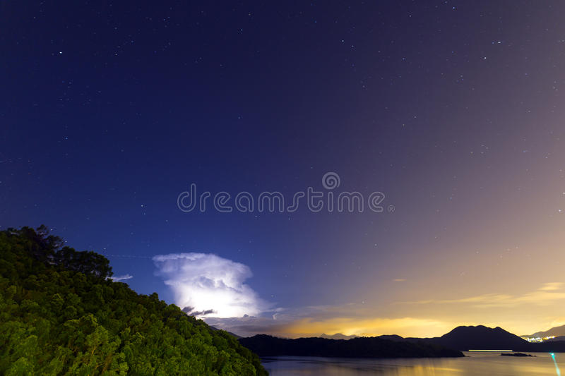Lightening at night in a clear sky with huge amount of stars royalty free stock image
