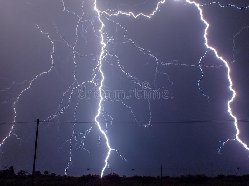 Lightening strikes in night sky. Dramatic lightening bolts in night sky with utility lines and pole in rural field. Blue, country, countryside, electric royalty free stock images