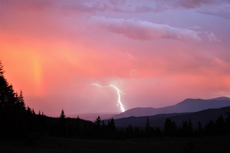 Lightening at Sunset. A thunderstorm at sunset causes lightening to strike the forest near Prospect Oregon while a rainbow begins to form. The lightening caused stock images