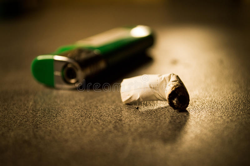 Lighter and smoked cigarette stock images