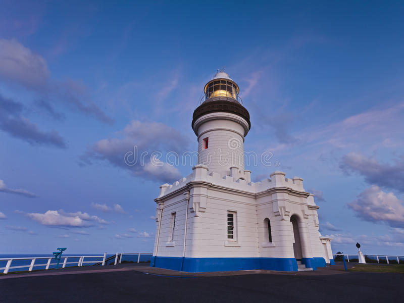 LightH Byron Bay Set. White historic lighthouse building at sunset illuminated lamp light source shining nautical landmark in Byron Bay, NSW Australia top of the royalty free stock image