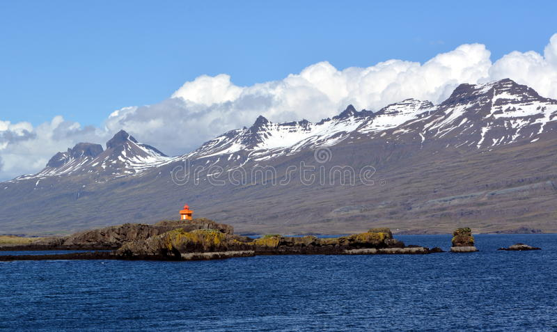A lighthouse against the background of the Snowy peaks of the basaltic mountains of the eastern fjords in Iceland stock photo