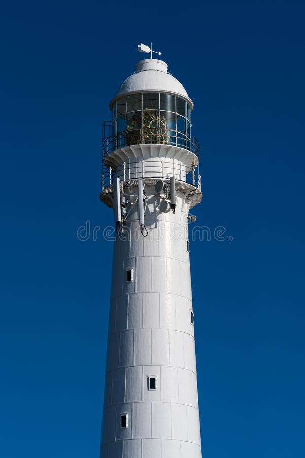 Vertical close up of a lighthouse against a blue sky. A lighthouse against blue sky in Kommetjie, Cape Town, South Africa stock images