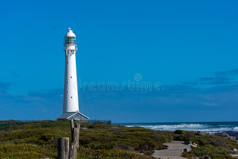 Lighthouse against blue sky with vegetation in foreground. stock images