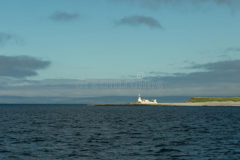 Lighthouse on the Aran Islands. View of a lighthouse on an Aran Island from the sea in Ireland royalty free stock image