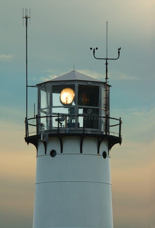 Lighthouse with beacon shining stock photos