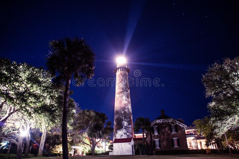 Lighthouse beams emitting against the night sky stock photo