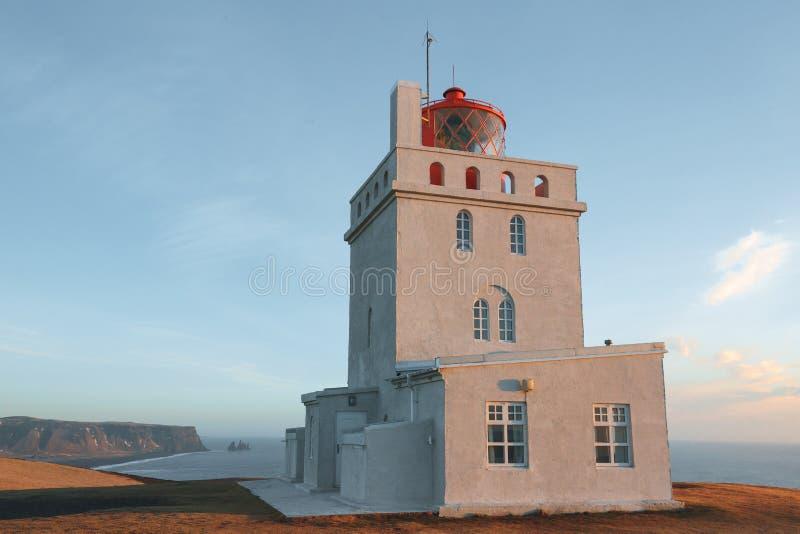 Lighthouse at beautiful icelandic seashore at sunny day, vik dyrholaey, reynisfjara. Beach, iceland royalty free stock image
