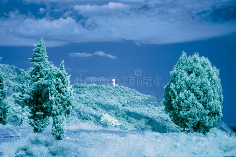 Lighthouse behind several cypress trees. Lighthouse in the village of Morskoye, Crimea, behind several cypress trees. Infrared photo. Pseudo color russia summer stock photos