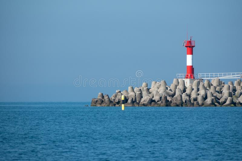Lighthouse on a breakwater in the blue sea royalty free stock photo