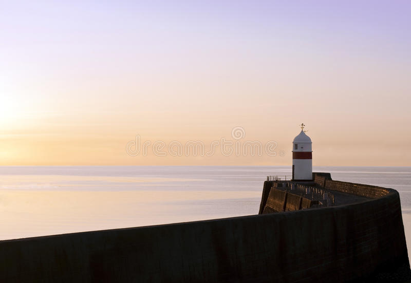 Download Lighthouse With Breakwater Wall At Sunrise Stock Photo - Image: 13844724