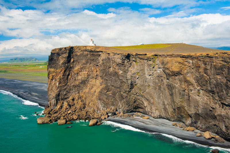 Lighthouse at cape Dyrholaey. Small lighthouse on the cliff at the cape Dyrholaey, the most southern point of Iceland stock photo
