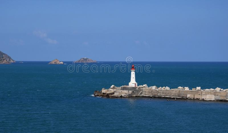 Lighthouse on a cape. Lighthouse in the sea. stock images