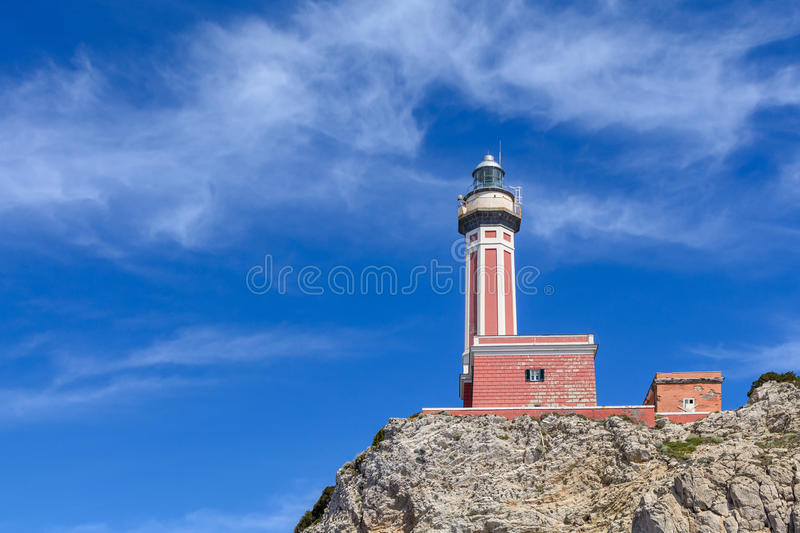 Lighthouse on a cliff in day time. Horizontal image with red and. White lighthouse on a cliff in summer time royalty free stock photos