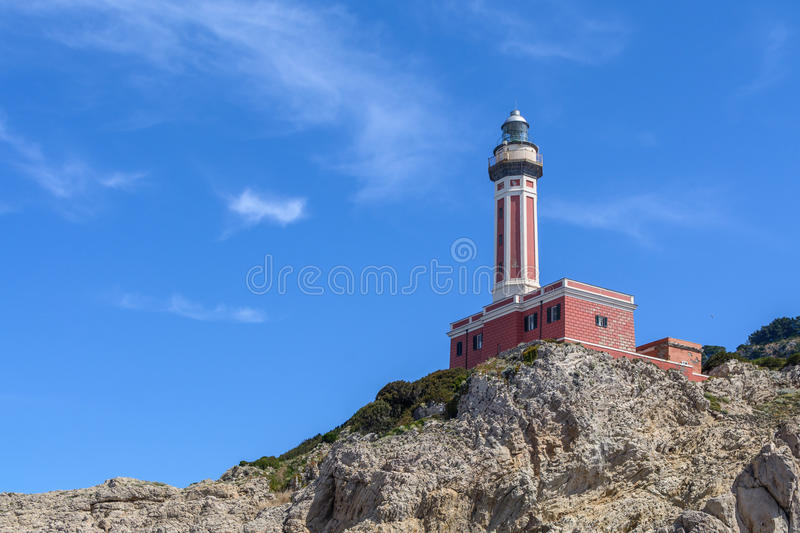 Lighthouse on a cliff in day time. Horizontal image with red and. White lighthouse on a cliff in summer time royalty free stock photo