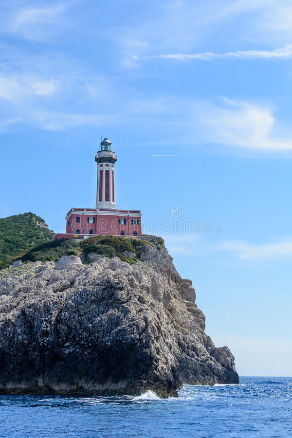 Lighthouse on a cliff in day time. Vertical image with red and w. Hite lighthouse on a cliff in summer time stock photography