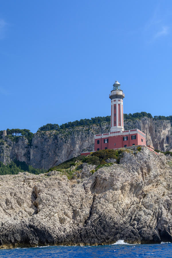 Lighthouse on a cliff in day time. Vertical image with red and w. Hite lighthouse on a cliff in summer time stock images