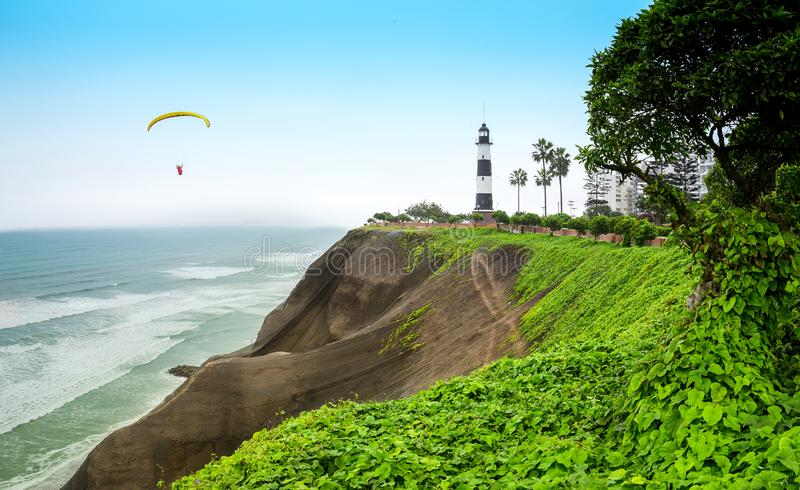 Lighthouse on the cliff edge in Miralfores distric in Lima, Peru. View at the lighthouse by the cliff edge in Miraflores with parachutist in the background stock photo