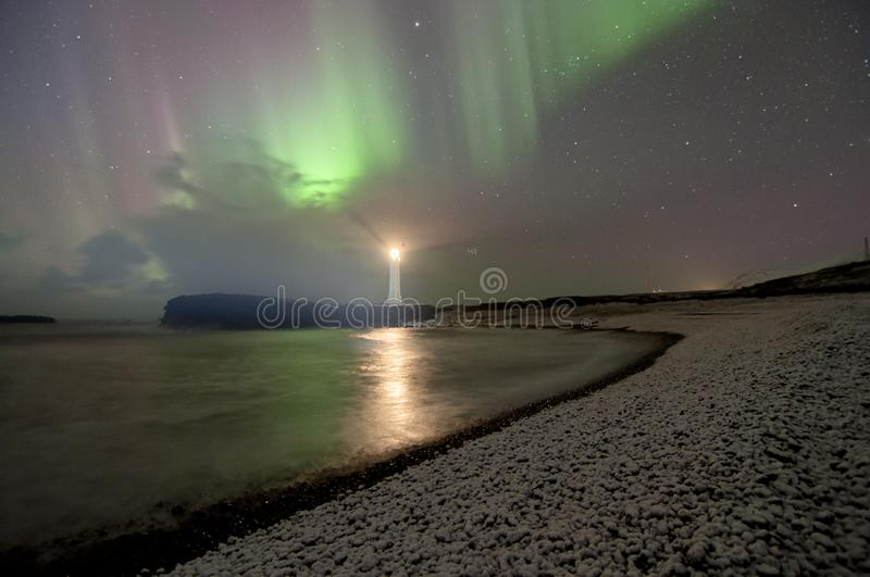 Lighthouse on a cliff  guiding the fishermen in Iceland under northern lights in snowy beach stock image