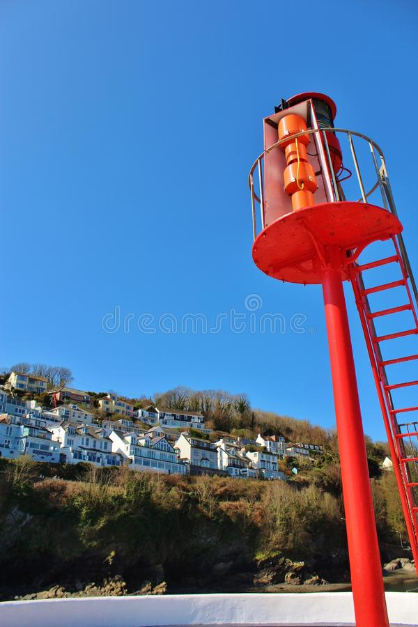 Lighthouse with cliff top houses, Looe Cornall UK stock images